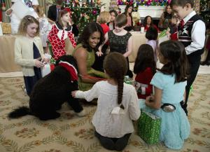 First lady Michelle Obama with dogs Bo, left, and Sunny, behind at right, are surrounded by children in the State Dining Room of the White House in Washington, Wednesday, Dec. 2, 2015, where they made holiday crafts and treats during a preview of the 2015 White House holiday decor. (AP...
