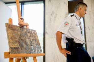 An officer stands guard next to Pablo Picasso's painting entitled La Coiffeuse, Thursday, Aug. 13, 2015, at the French Embassy, in Washington.