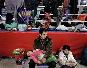 A Chinese couple with their child  inside a stadium, which was converted to a temporary shelter following Monday's powerful 7.9 magnitude earthquake in Mianyang, Sichuan province, China, Tuesday, May 13, 2008.