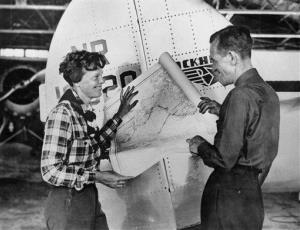 Aviator Amelia Earhart and navigator Fred Noonan pose with a map of the Pacific Ocean showing the planned route of their round-the-world flight.