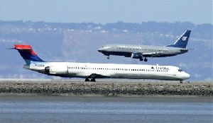In this April 15, 2008 file photo, a Delta Airlines plane prepares to take off from a runway as a United Airlines plane, rear, lands at San Francisco International Airport in San Francisco.