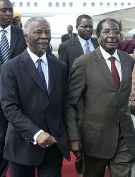 President Robert Mugabe, right,  welcomes South African President Thabo Mbeki, left, of South Africa at Harare International Airport, Saturday, April, 12, 2008.