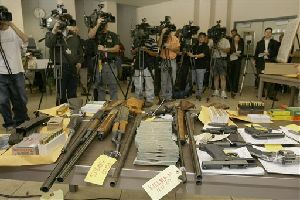 Members of the media gather to photograph confiscated guns and money seized during a series of raids on a violent South Los Angeles street gang.