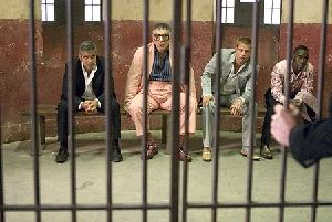 George Clooney, Elliott Gould, Brad Pitt, and Don Cheadle behind bars in Ocean's Twelve.