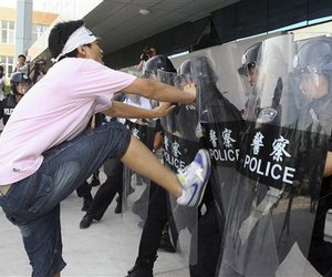 A mock protester attacks Chinese police officers in anti-riot gear during a drill in front of the Olympic Games Village. The Chinese have warned visitors that protests are prohibited.