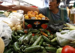 A women sells produce in front of a pile of jalapeno peppers in Mexico City, Friday, July 25, 2008.
