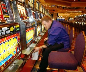 Casino worker James Askins cleans slot machines at the Trump Taj Mahal in Atlantic City, N.J., in this July 7, 2006 file photo.