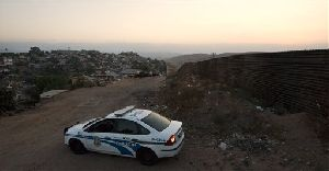 A police car patrols at the Libertad neighborhood, near the U.S.-Mexico border in Tijuana, Mexico, Thursday, June 26, 2008.