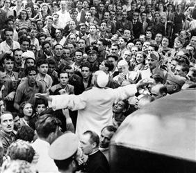 A crowd gathers around Pope Pius XII, his arms outstretched, during his inspection tour of Rome after a 1943 American air raid.
