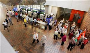 Voters wait to check in before they vote in Miami, Monday, Oct. 20, 2008. The polls opened for the first day of early voting in the state of Florida.