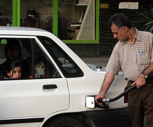An Iranian man pumps gas as his family sit in the car, at a station in Tehran, Iran, Tuesday, May 22, 2007.