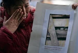 A woman holding a picture of a trapped cat cries as she takes part in today's protest.
