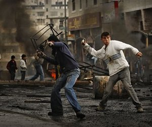 Palestinian protesters throw stones during clashes with Israeli troops in the Shuafat refugee camp, on the outskirts of Jerusalem, Monday, Dec. 29, 2008.