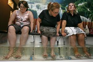 Women indulge in a fish pedicure treatment at Yvonne Hair and Nails salon in Alexandria, Va., July 17, 2008.