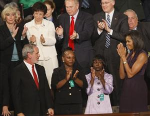 Michelle Obama and Ty'Sheona Bethea, second from left, applaud during President Barack Obama's address to a joint session of Congress yesterday.