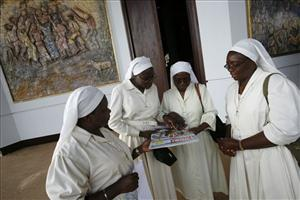 Cameroonian nuns look at a special edition magazine on the visit of Pope Benedict XVI as they wait for the start of rehearsals for Wednesday's Vespers ceremony with the pope.