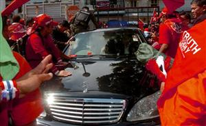 Red-shirted anti-government protesters and supporters of ousted Prime Minister Thaksin Shinawatra attack the car of Prime Minister Abhisit Vejjajiva with clubs and various objects.
