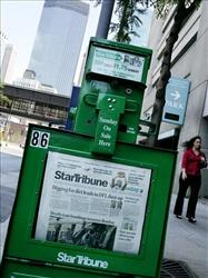 In this Wednesday, July 12, 2006 file photo, the Minneapolis skyline rises in the background of a Star Tribune newspaper vending machine.