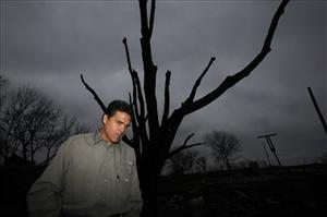 Texas Gov. Rick Perry walks in a area destroyed by recent wildfires during a tour in Stoneburg, Friday, April 17, 2009. He asked today for federal help in fighting a potential swine flu outbreak.