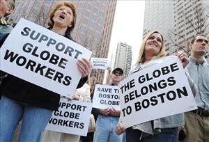 Boston Globe workers hoist placards at a rally Friday.