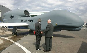 Two visitors chat next to the RQ4 Block20 Global Hawk, a Northrop Grumman American company made, high altitude unmanned aerial reconnaissance system, designed to provide military field commanders with imagery of large geographic areas, at the Bourget airport, during the 47th Paris Air Show in Le Bourget, north of Paris,...