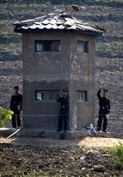 North Korean soldiers gestures to a Chinese tourist boat from an outpost along the China-North Korea border today.