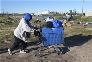 A woman uses a shopping cart to move her possessions from a homeless encampment   in Sacramento, Calif., last month.