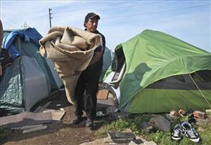 Danny Gonzalez  moves a carpet out of a tent as he helps a friend move from a homeless encampment in Sacramento, Calif., Monday, April 13, 2009.