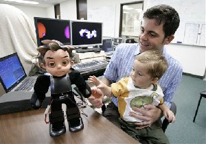 David Hanson, right, holds his son Zeno on his lap as the two look at Hansons' Robot creation, also named, Zeno, at his office in Richardson, Texas, Thursday, Sept. 6, 2007.  (AP Photo/Tony Gutierrez)