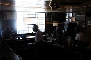 Angelo Cammarata talks with a patron at his bar in West View, Pa.