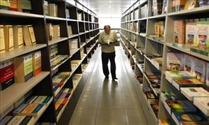A man checks books at Dar Al-Hadi Publishing House, one of Lebanon's most prominent publishing houses of religious Shiite books. The firm's financier owner has been charged with fraud.