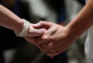 Same-sex couple Amber Weiss and Sharon Papo hold hands as they get married at San Francisco City Hall June 17, 2008 in San Francisco, California.