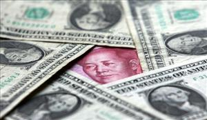 Dollars and yuan notes are seen at a bank   in Beijing, China.