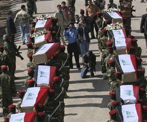 Iraqi soldiers carry coffins with the remains of Iraqi soldiers killed during an eight-year war between Iran and Iraq at the border crossing of Al-Shalamjah, Iraq, Sunday, Nov. 30, 2008.