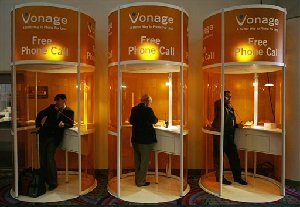 Attendees make free phone calls over VoiP at the Vonage booth at the 2007 International Consumer Electronics Show (CES) in Las Vegas, in this Jan. 10, 2007 file photo. Internet telephone company Vonage Holdings Corp. on Thursday, Aug. 9, 2007 reported a much reduced loss for the second quarter as...