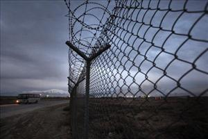 A bus passes a security fence at Bagram Air Base in Bagram, Afghanistan.