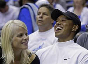 In this June 11, 2009 file photo, Elin Nordegren talks to her husband, golfer Tiger Woods during Game 4 of the NBA basketball finals in Orlando, Fla.