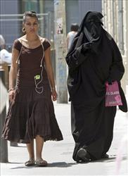 Two women, one wearing the niqab, a veil worn by the most conservative Muslims that exposes only a woman's eyes, walk side by side in Marseilles.