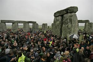 People dance as they celebrate the summer solstice shortly after 04.58, at the Stonehenge monument, England, early Saturday June 21, 2008.