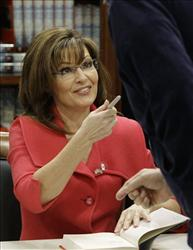 FILE - In this file photo taken Dec. 1, 2009, Sarah Palin talks with a supporter as she autographs copies of her book Going Rogue during a book signing at the Costco in Tempe, Ariz.  A reader-submitted question about the book Going Rogue is being answered as part of an...