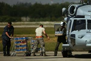 US soldiers load a military helicopter with water at the Toussaint L'ouverture international airport?in Port-au-Prince, Friday, Jan. 15, 2010.