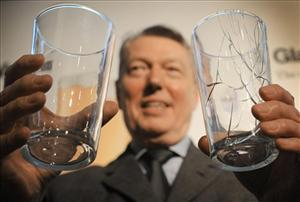 British Home Secretary Alan Johnson holds two prototype pint glasses.