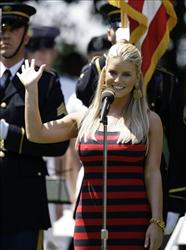 Jessica Simpson waves to the crowd after singing the national anthem during opening ceremonies for the AT&T National golf tournament at Congressional Country Club, July 1, 2009, in Bethesda, Md.