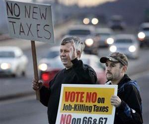 Demonstators hold anti-tax signs along the Ferry St. Bridge in Eugene, Ore., Jan. 26, 2010, urging voters to reject ballot initiatives on taxing the wealthy and businesses.