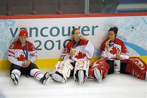 Canada's Marie-Philip Poulin, left to right,  Kim St-Pierre and  Charline Labonte drink beer on the ice with their gold medals after Canada defeated the US yesterday.