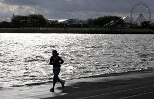 A jogger is silhouetted against Chicago's Navy Pier on the Lake Michigan shoreline Wednesday, Sept. 30, 2009 in Chicago.