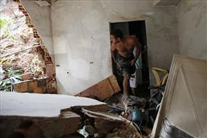 A resident searches for recoverable items in his home after it was damaged by heavy rain and a landslide in the Caixa D'agua area in Niteroi, Brazil.