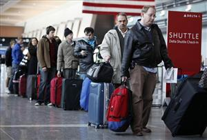 Passengers wait to check in at Logan International Airport in Boston.
