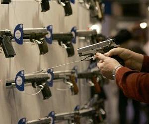 A woman points a handgun with a laser sight on a wall display of other guns during the National Rifle Association convention Friday, April 13, 2007, in St. Louis.