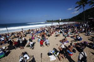 People on the beach watch during the first round of the Quiksilver in Memory of Eddie Aikau Competition big wave surfing contest on December 8, 2009 in Waimea, Hawaii.